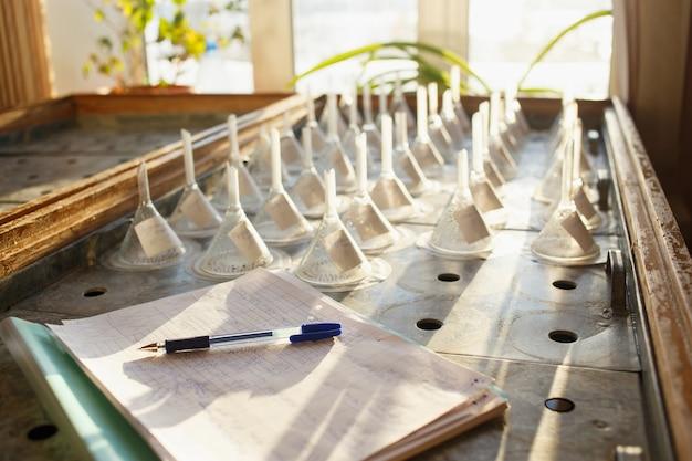 Table De Germination Avec Graines Dans Des Entonnoirs Filtrants Et Journal De Bord Avec Stylo Photo Premium