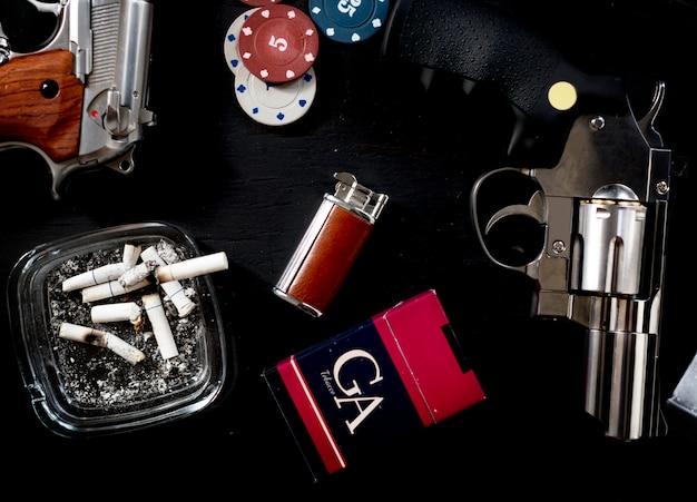 Table de jeu et de gangster mise en place avec des cigarettes et des armes à feu. Photo Premium