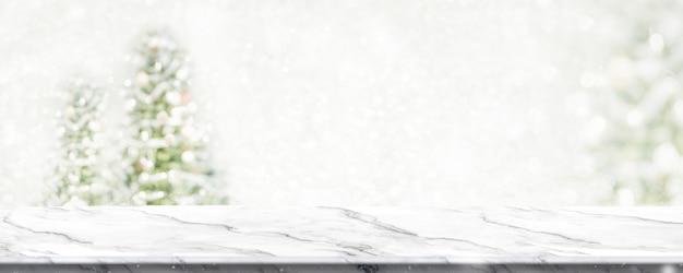 Table En Marbre Avec Flou De Lumière De Chaîne D'arbre De Noël Flou Fond Avec Neige Photo Premium