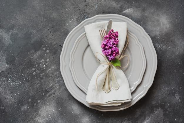 Table mise en place avec fleurs lilas pourpres, couverts sur fond vintage. Photo Premium