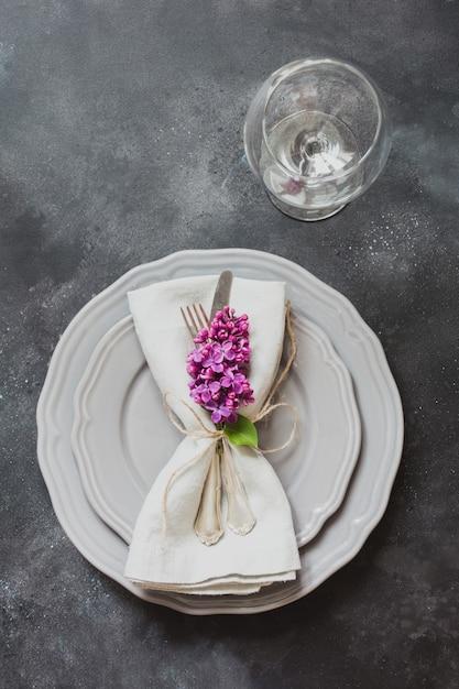 Table mise en place avec des fleurs lilas roses, argenterie sur fond vintage. Photo Premium