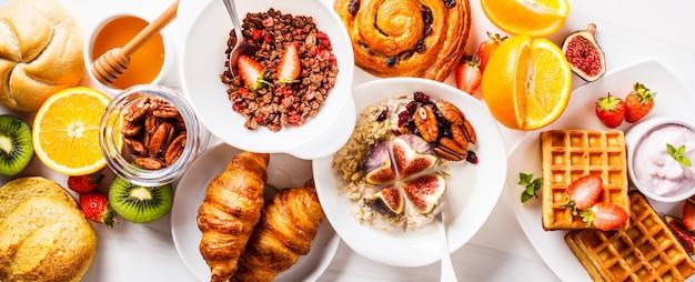 Table de petit déjeuner avec des flocons d'avoine, des gaufres, des croissants et des fruits. Photo Premium