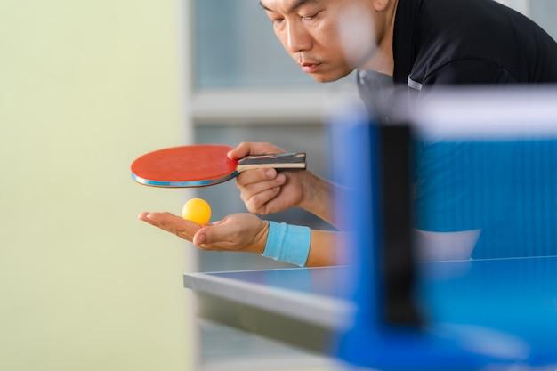Table de ping-pong, homme jouant au tennis de table avec raquette et balle dans une salle de sport Photo Premium