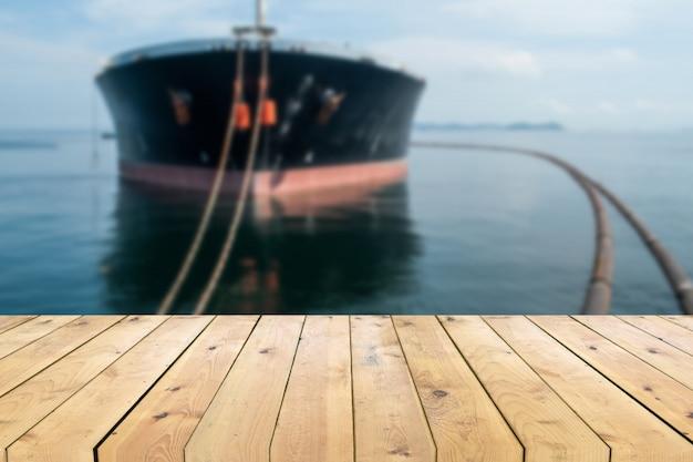 Table de planche de bois vide avec navire pétrolier navire flou fond Photo Premium