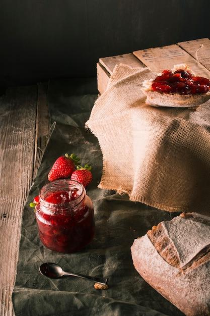 Table avec des restes de petit-déjeuner et des confitures de fraises Photo gratuit