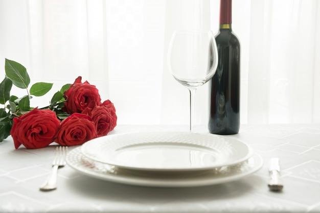 Table saint valentin avec bouquet de roses rouges et vin. Photo Premium
