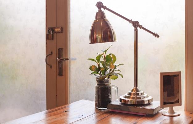 Table de salle de lecture en bois rustique avec une lumière chaude et naturelle éclairée par une porte vitrée. Photo Premium