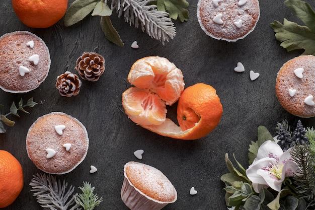 Table avec satsumas, muffins saupoudrés de sucre et biscuits étoile de noël sur noir Photo Premium