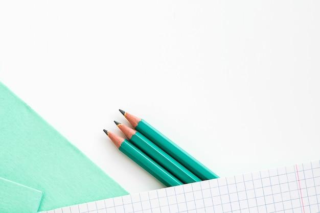 Sur La Table Se Trouve Un Cahier Ouvert Dans Une Cage. Crayons à Côté Du Cahier D'école. Cahier D'école Photo Premium