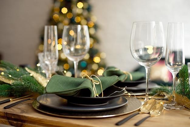 Table servie pour le dîner de noël dans le salon, vue rapprochée, réglage de la table, décoration de noël Photo Premium