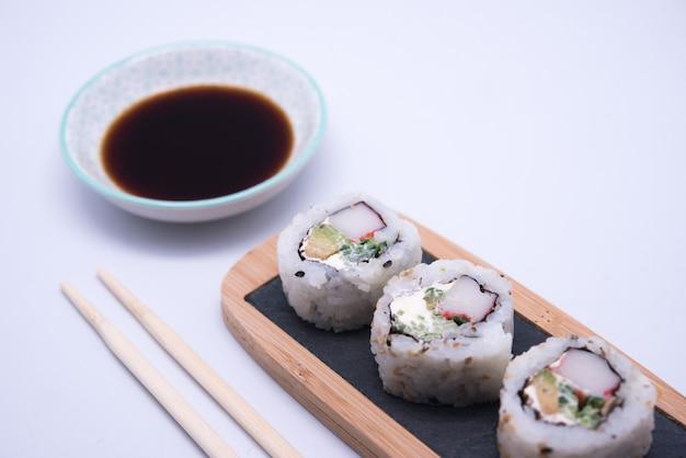 Table avec sushi et baguettes avec bol de sauce soja Photo Premium