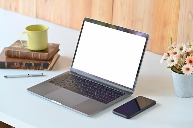 Table de travail blanche avec ordinateur portable à écran blanc, fleur, livres et tasse à café Photo Premium