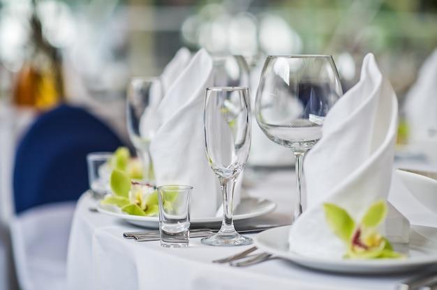 Table avec des verres, des assiettes et des serviettes blanches, fleur verte, dîner au restaurant Photo Premium