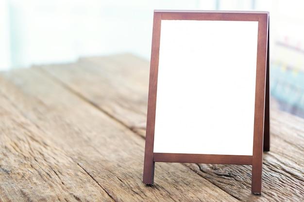 Tableau blanc publicitaire avec chevalet debout sur une table en bois Photo Premium