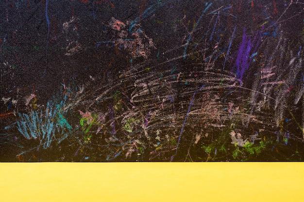 Tableau noir abstrait peint avec des crayons de couleur et une table jaune Photo Premium