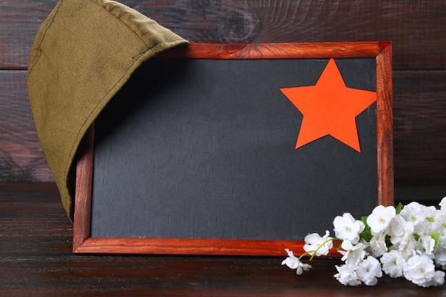 Tableau noir, casquette militaire et étoile rouge sur une table. journée du défenseur de la patrie et du 9 mai. Photo Premium