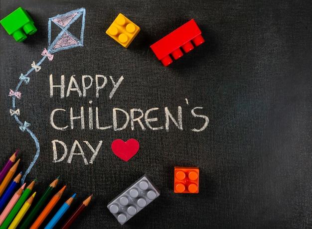 Tableau noir écrit «happy children's day» et dessin de cerf-volant avec pièces d'assemblage dispersées et crayons de couleur Photo Premium