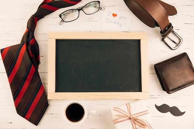 Tableau noir parmi les accessoires masculins près de cadeau et tasse de boisson Photo gratuit