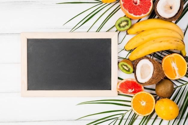 Tableau noir près de la plante laisse avec des fruits tropicaux frais Photo gratuit