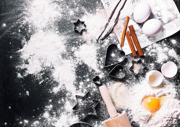 Tableau noir rempli de farine et les œufs avec des décorations de noël Photo gratuit