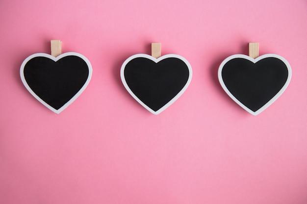 Tableau trois craie pour les notes en forme de coeur sur fond rose Photo Premium