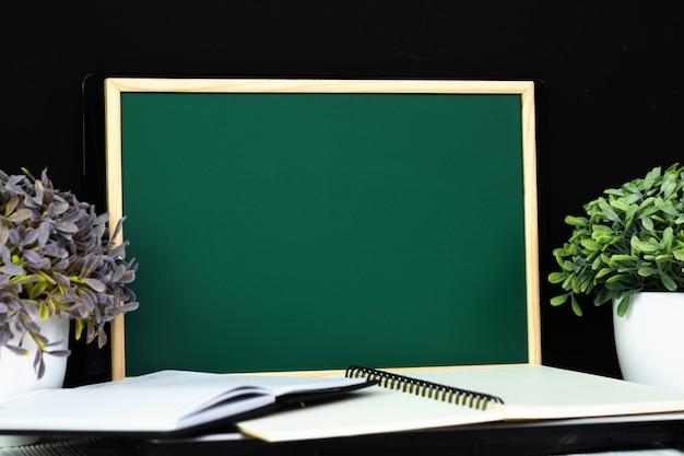 Tableau vert avec pile de pape de cahier Photo Premium