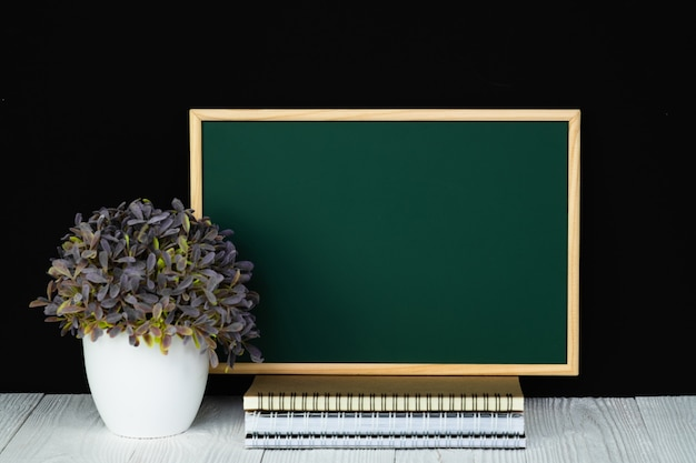 Tableau vert avec une pile de papier de cahier, de papeterie ou de fournitures scolaires. Photo Premium
