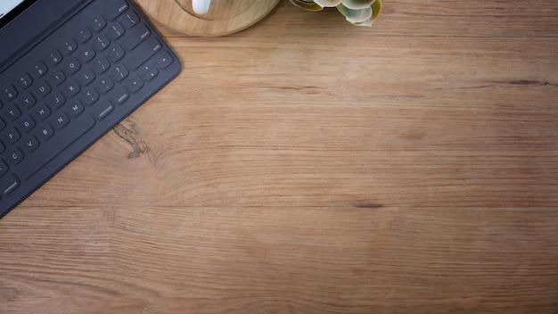 Tablette avec accessoires de bureau smart keyboard sur l'espace de table et de copie en bois Photo Premium