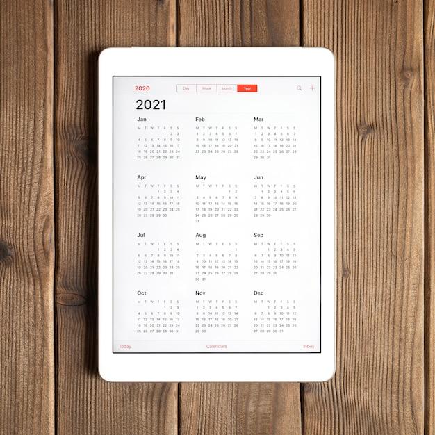 Une Tablette Avec Un Calendrier Ouvert Pour 2021 Ans Sur Un Fond De Table En Bois. Carré Photo Premium