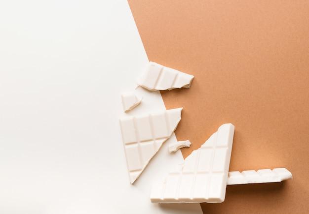 Tablette de chocolat blanc cassée sur fond bicolore Photo gratuit