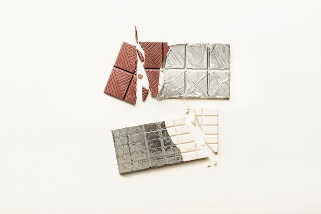 Tablette de chocolat cassée blanche et brune enveloppée dans du papier d'aluminium sur un fond uni Photo gratuit