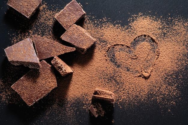 Tablette de chocolat cassée sur fond noir, cœur en poudre de cacao peint Photo Premium