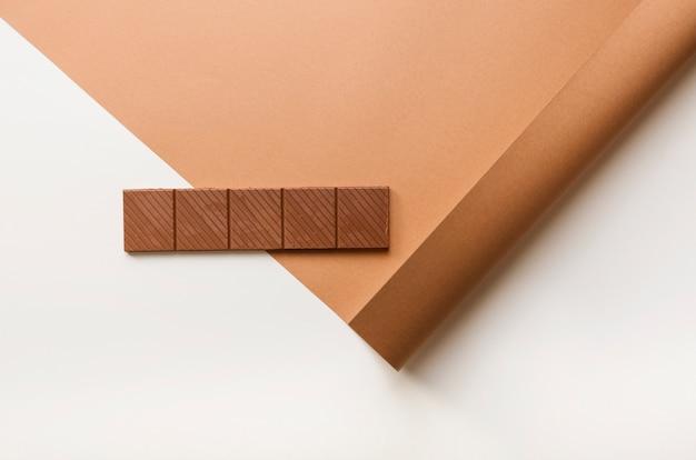 Tablette de chocolat sur du papier cartonné contre fond blanc Photo gratuit