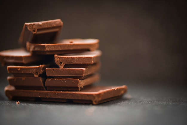 Tablette De Chocolat Empilée Sur Le Fond Sombre Pièces De Chocolat Photo Premium