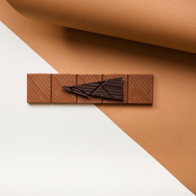 Tablette de chocolat noir et marron sur papier cartonné sur fond blanc Photo gratuit
