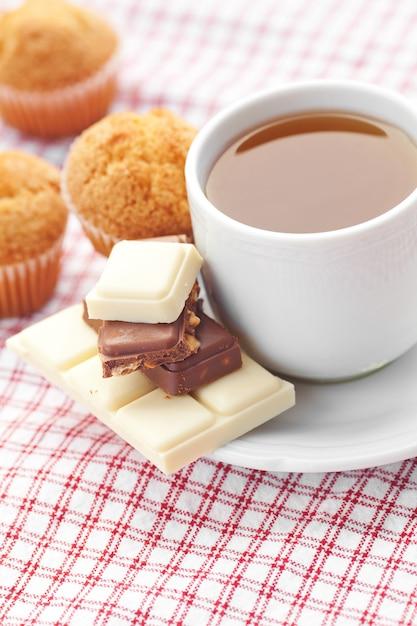 Tablette de chocolat, thé et muffins sur tissu à carreaux Photo Premium