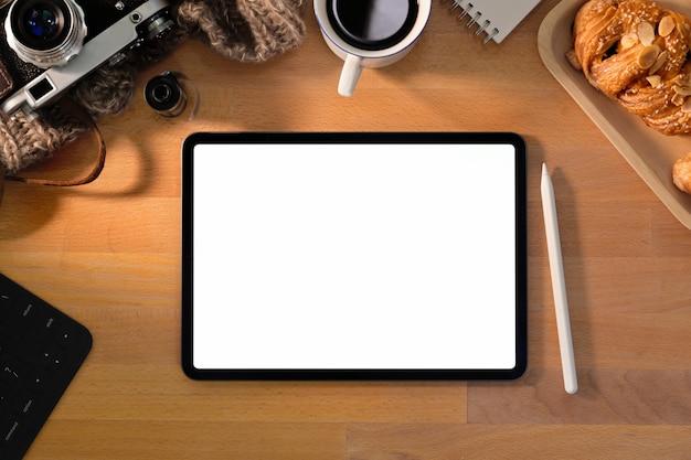 Tablette écran blanc sur un bureau élégant en bois avec fournitures de photographe créatif Photo Premium