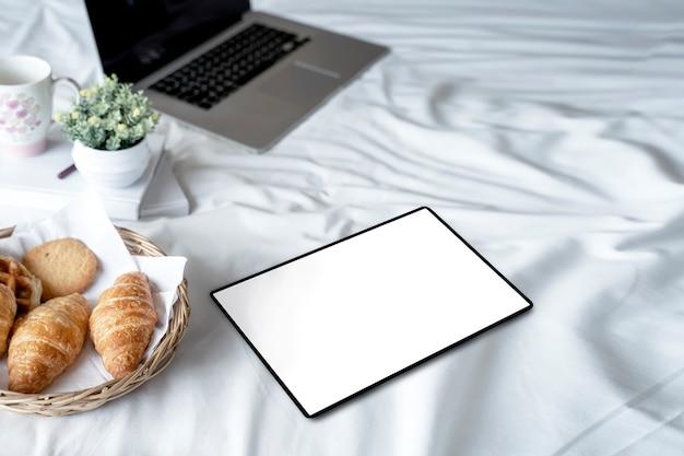 Tablette écran blanc avec du pain sur des draps blancs. Photo Premium
