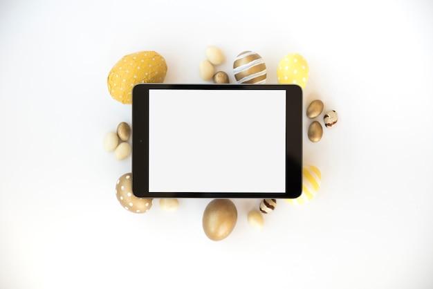 Tablette avec écran blanc sur oeufs de pâques Photo gratuit