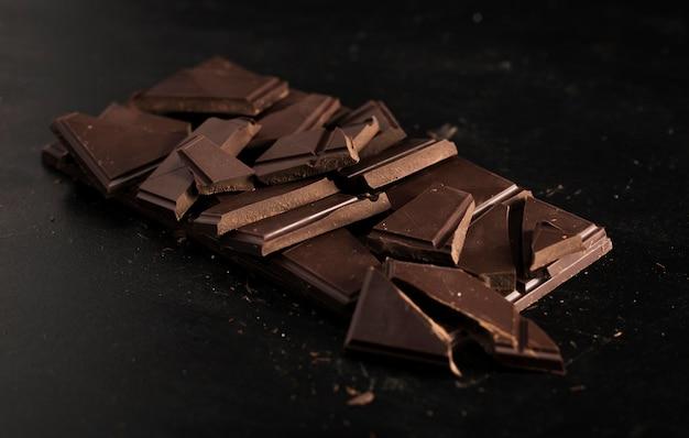Tablette écrasée de chocolat sur fond noir Photo gratuit