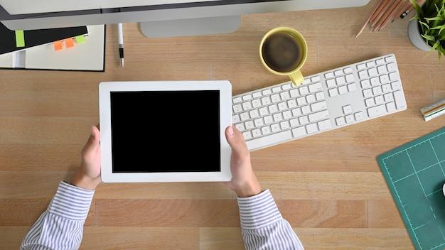 Tablette d'espace de travail vue de dessus tenant sur un homme mains avec dessus du bureau table. Photo Premium
