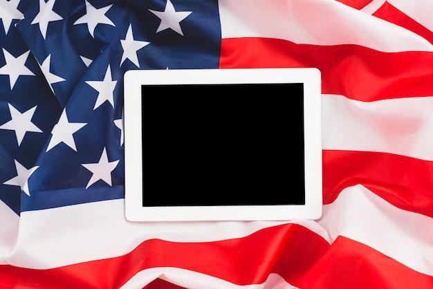 Tablette éteinte sur drapeau américain Photo gratuit
