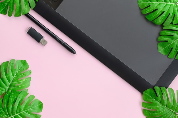 Tablette graphique et stylo, carte mémoire et monstera leafs Photo Premium