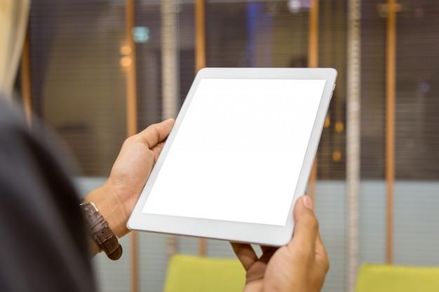 Tablette de maquette sur les mains de l'homme d'affaires affichent vide sur la table de la maison avec fond flou Photo Premium