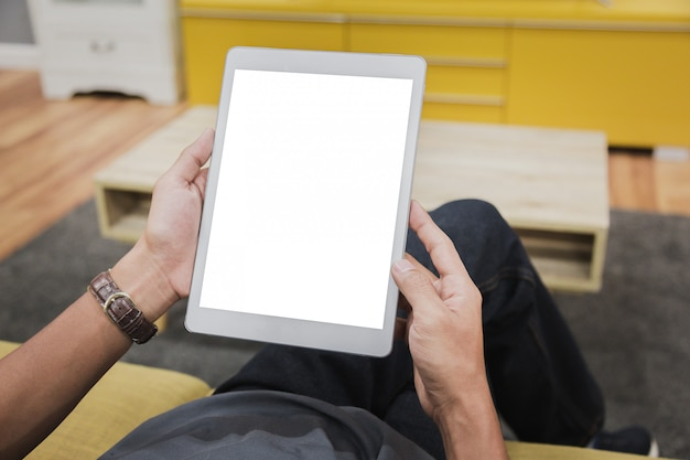 Tablette de maquette sur les mains de l'homme d'affaires affichent vide sur la table de la maison. Photo Premium