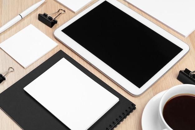 Tablette numérique avec bloc-notes, fournitures et tasse à café sur le bureau. Photo Premium