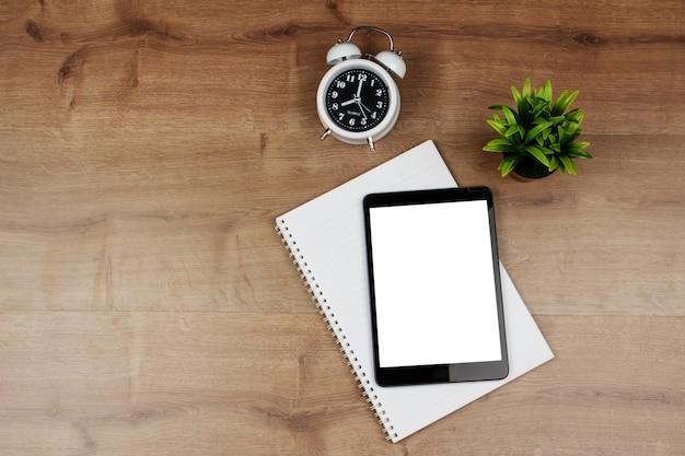 Tablette numérique avec écran blanc et cahier sur le bureau en bois Photo Premium