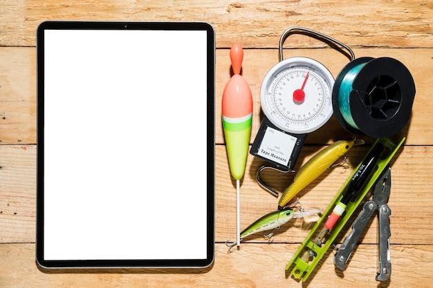 Tablette numérique écran blanc avec des équipements de pêche sur un bureau en bois Photo gratuit