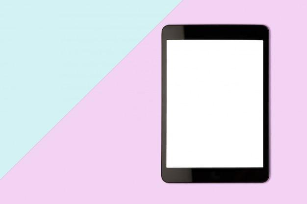 Tablette numérique avec un écran blanc sur fond de couleur pastel, photo de mise à plat Photo Premium