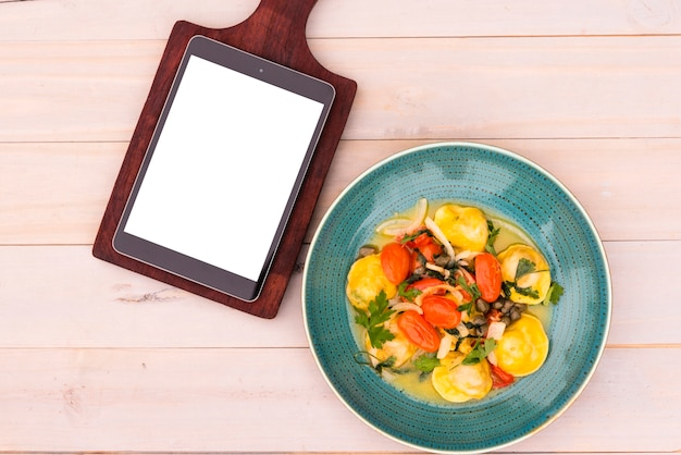 Tablette numérique d'écran blanc sur une planche à découper et de délicieuses pâtes de raviolis dans une assiette sur une table en bois Photo gratuit